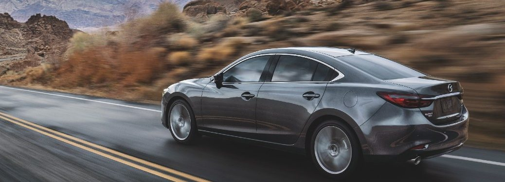 grey 2021 Mazda6 driver side rear fascia driving fast on highway in rocky desert area