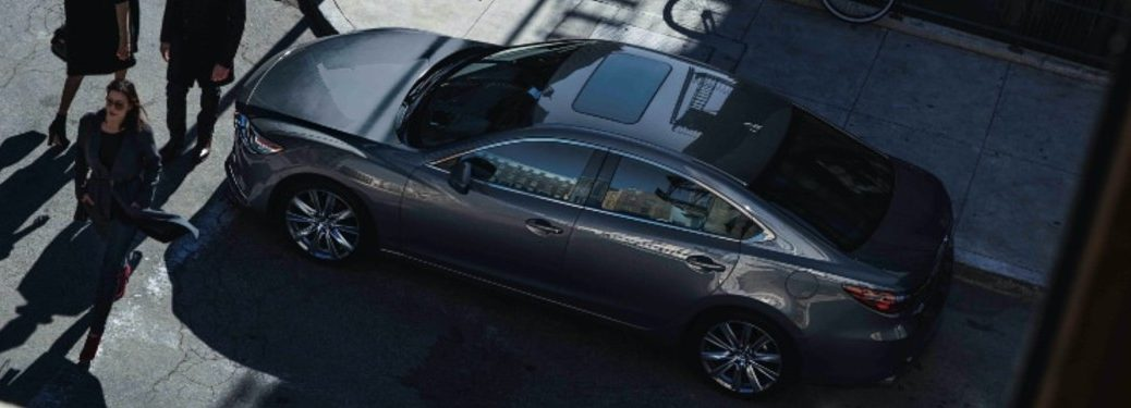 sky view of grey 2021 Mazda6 driver side waiting at intersection for people to cross street