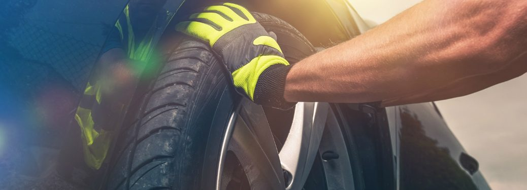 man wearing gloves with is hand on a tire