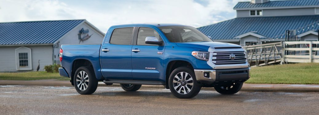 Blue 2018 Toyota Tundra parked in front of blue and white buildings