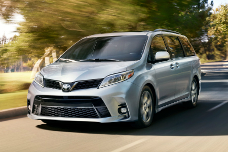 Silver 2018 Toyota Sienna driving by wooded area