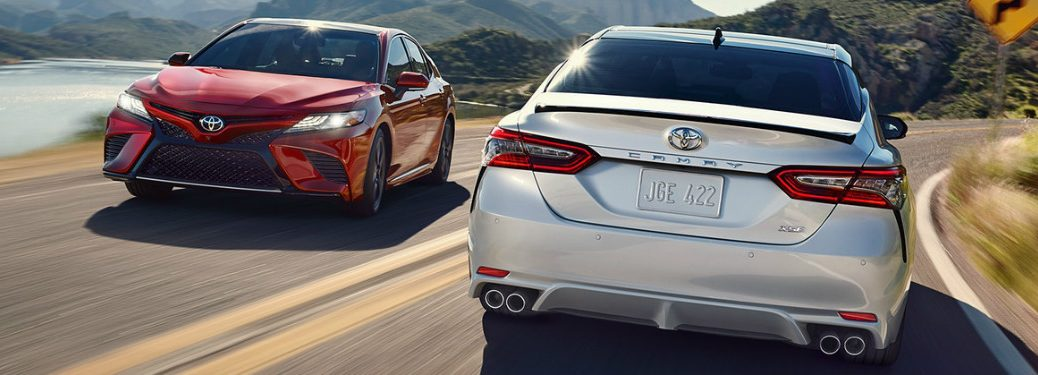 Red and white 2018 Toyota Camry models passing each other on the road