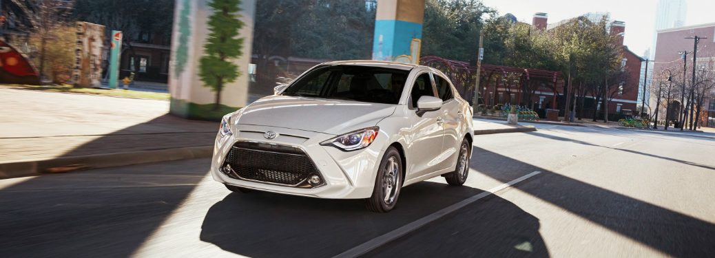 White 2019 Toyota Yaris driving under structure