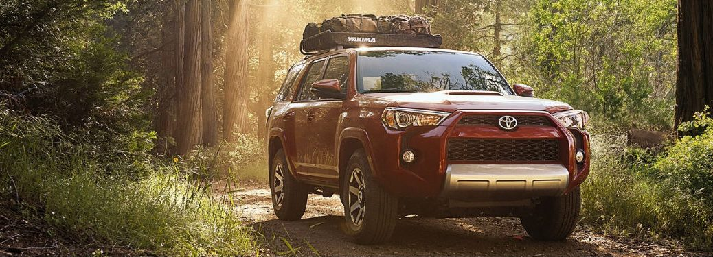 Red 2018 Toyota 4Runner driving off-road through forest
