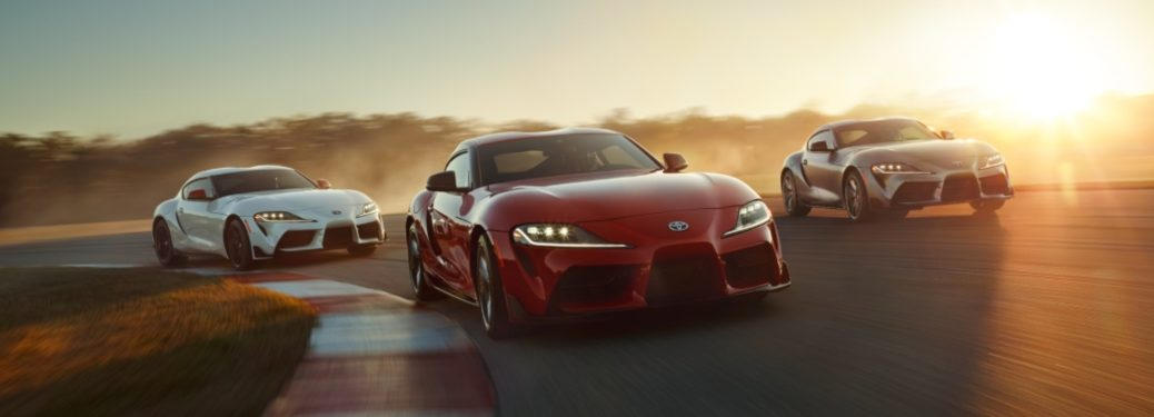 Three Toyota Supra models driving on track