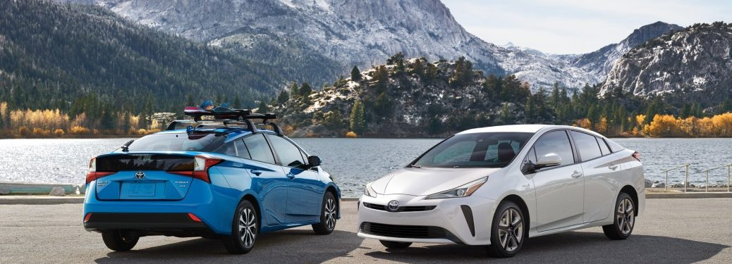 Blue and white 2019 Toyota Prius models parked in front of mountain range