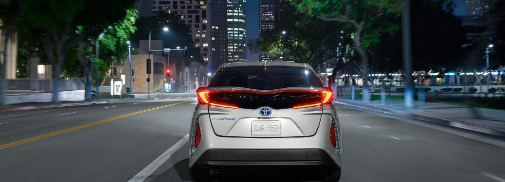 Rear view of a Toyota Prius Prime driving towards city