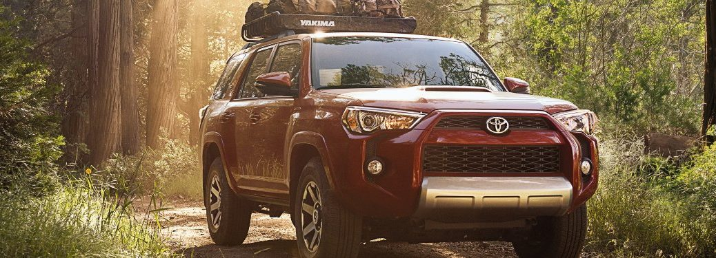 Red 2019 Toyota 4Runner driving in the woods