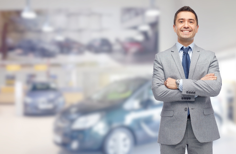 Car businessman standing in front of blurred out cars proudly