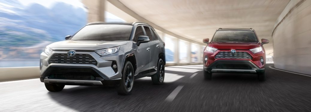 two 2021 RAV4 Hybrid models driving side-by-side