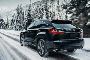 Black Lexus RX 350 drives up a snowy road among pines.