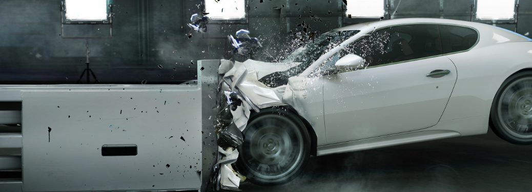 White vehicle slams into a metal barrier in some kind of crash test in a factory.