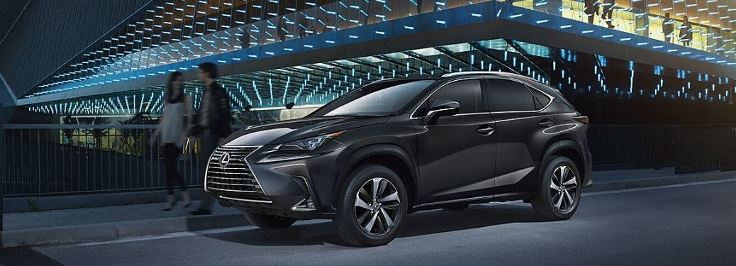 Black 2020 Lexus NX and Couple Next to Glass Modern Building