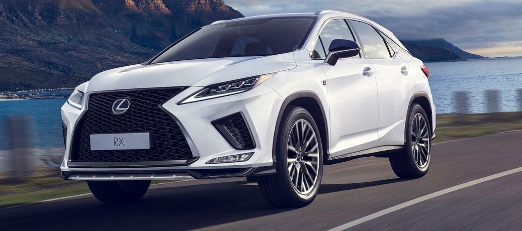 White 2020 Lexus RX drives up a coastal highway looking powerful.