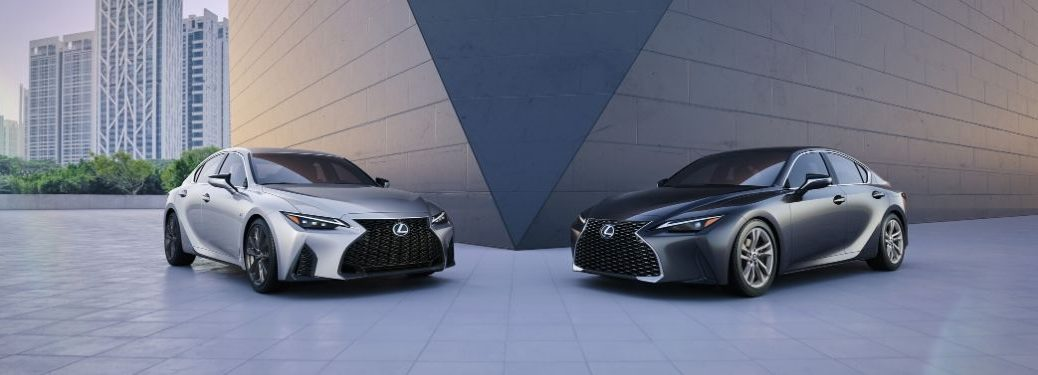 Silver and Gray 2021 Lexus IS Models Next to a Modern Building