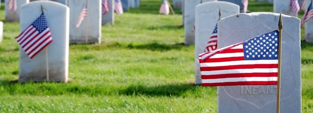 Headstones in a Cemetery with American Flags