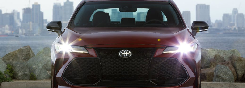 front end of red toyota avalon with headlights on