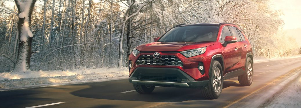 front view of red toyota rav4 driving on wooded road