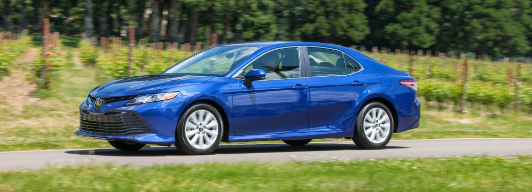 left side view of blue toyota camry driving