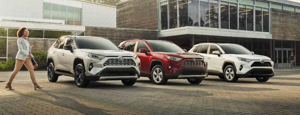 a woman walks towards a lineup of 2020 Toyota RAV4 models in silver, red, and white paint colors