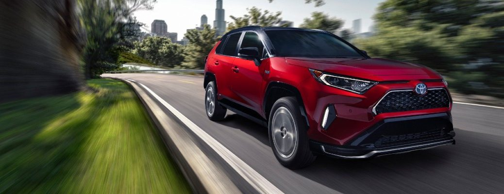 2021 Toyota RAV4 Prime exterior shot with red paint color driving on a highway road as a forest background blurs