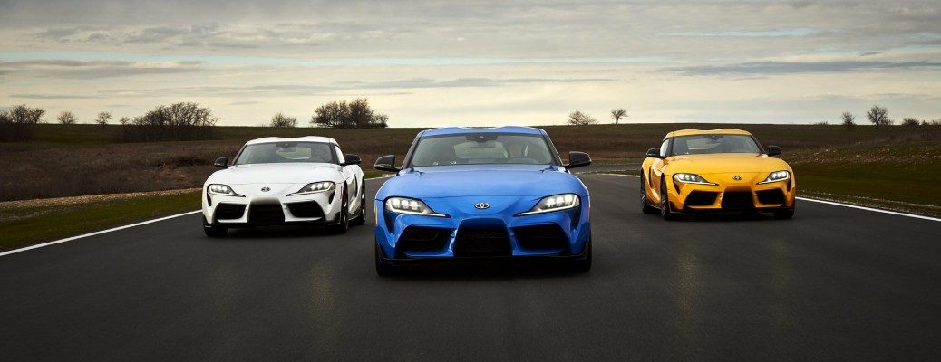 2021 Toyota GR Supra models in white, blue, and yellow driving side by side down a country highway