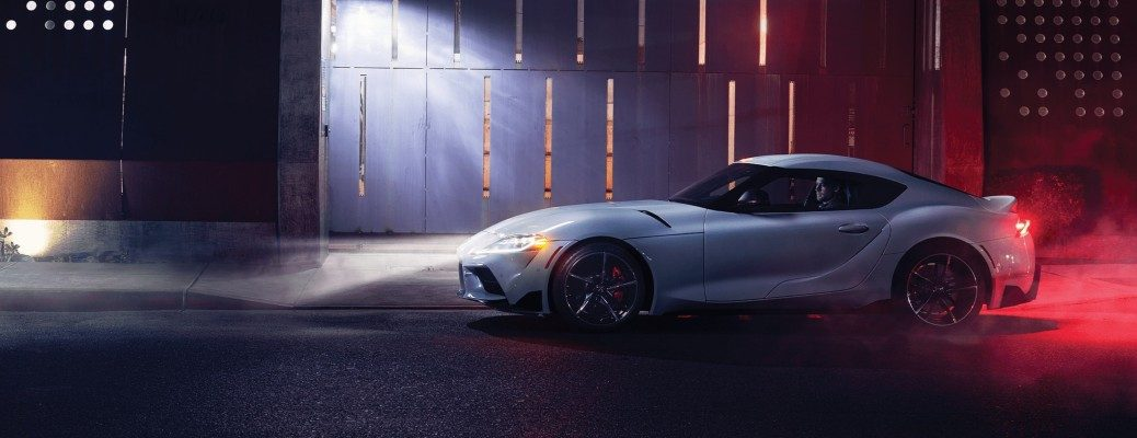 2021 Toyota GR Supra exterior side shot at night with headlights on parked outside a shipping yard