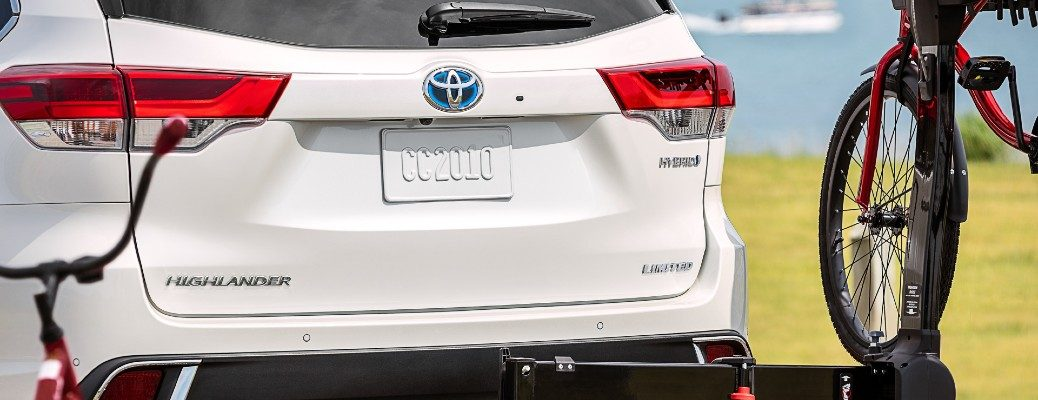 2020 Toyota Highlander Hybrid exterior rear shot with Blizzard Pearl paint color of back bumper, badging, trunk, taillights, and bike rack