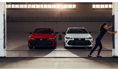 2020 Toyota Avalon models in red and white parked inside a hangar as a woman slides its door open