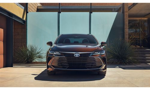 2020 Toyota Avalon Hybrid exterior front shot with dark red maroon paint color parked outside of a luxury house