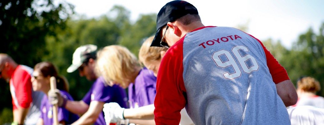 Toyota Motor Corporation serving our communities involvement banner with volunteers digging outside