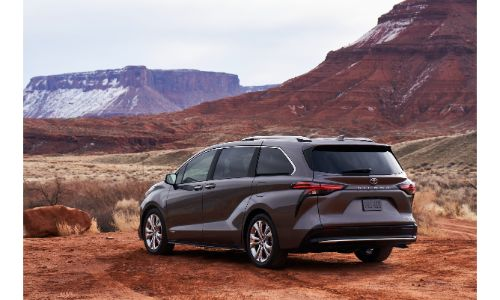 2021 Toyota Platinum exterior rear shot with gray paint color parked on dirt in front of rocky and snowy mountain hills