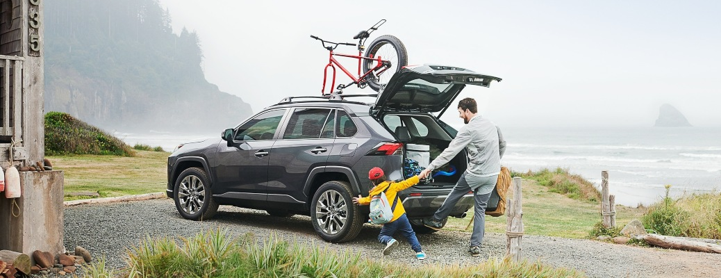 A father and child getting cargo out of a 2021 Toyota RAV4