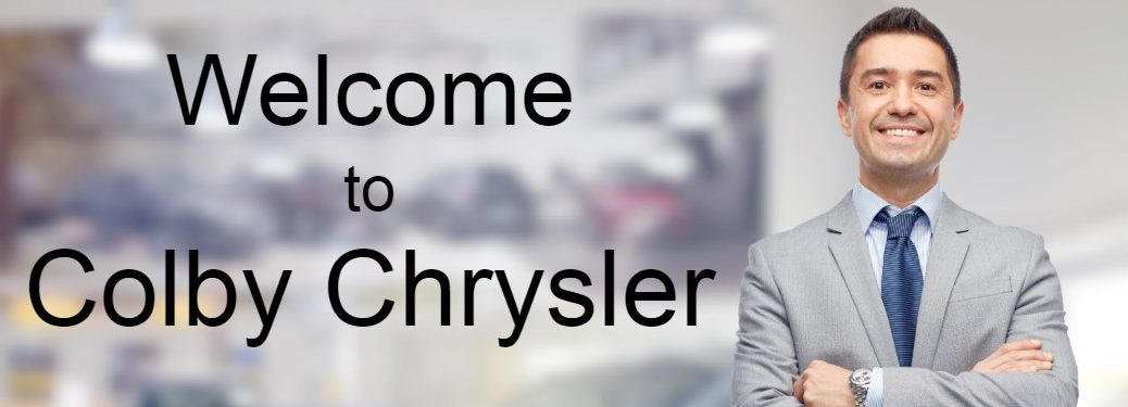 """Salesman smiling with his arms folding on right side in front of blurry background with the text """"Welcome to Colby Chrysler"""" on left side"""