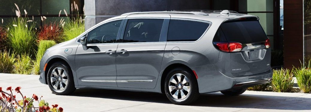 Rear driver angle of a grey 2019 Chrysler Pacifica parked in front of a building