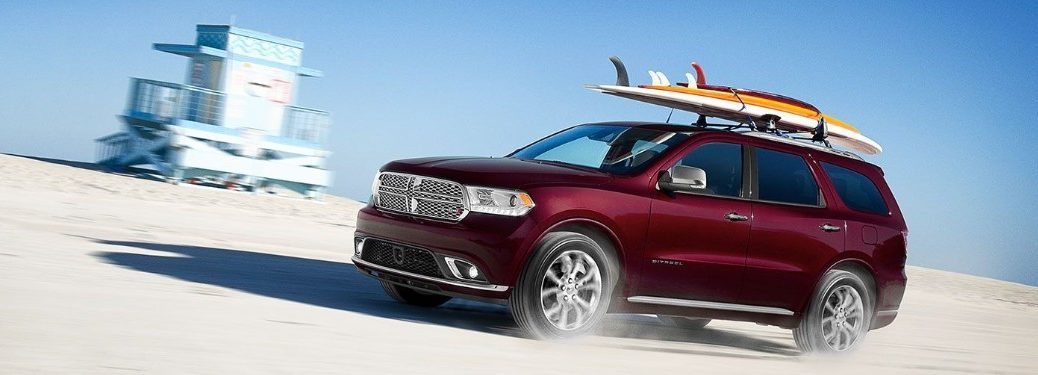Front driver angle of a red 2019 Dodge Durango with surfboards on its roof driving on a beach with a watchtower in the background