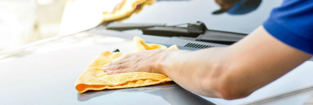 person scrubbing hood of a vehicle
