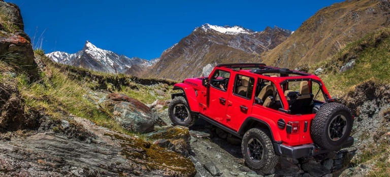 2020 Jeep Wrangler red back view climbing rocks