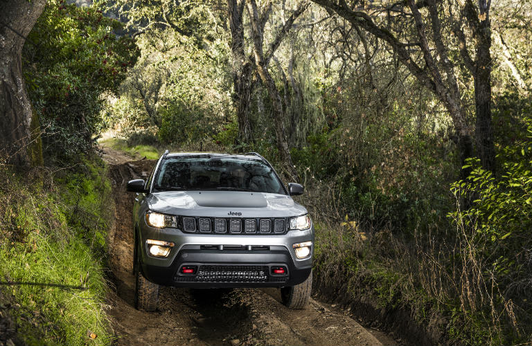 2018 Jeep Compass on a muddy road in the woods