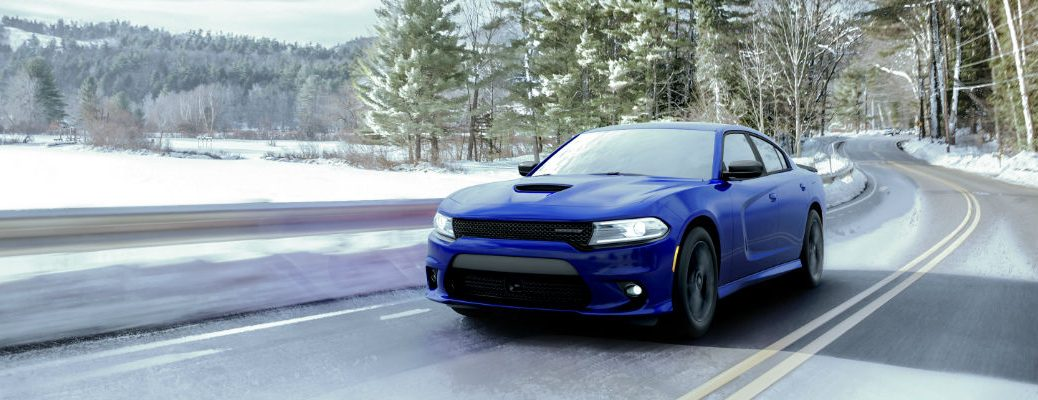 A photo of the 2020 Dodge Charger driving on a snowy road.