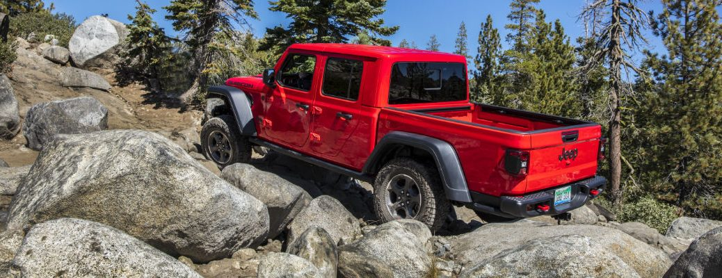 A photo of the 2020 Jeep Gladiator crawling over some rocks.