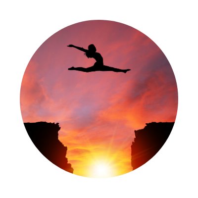 Silhouette of girl in a split leap over cliffs with sunset background