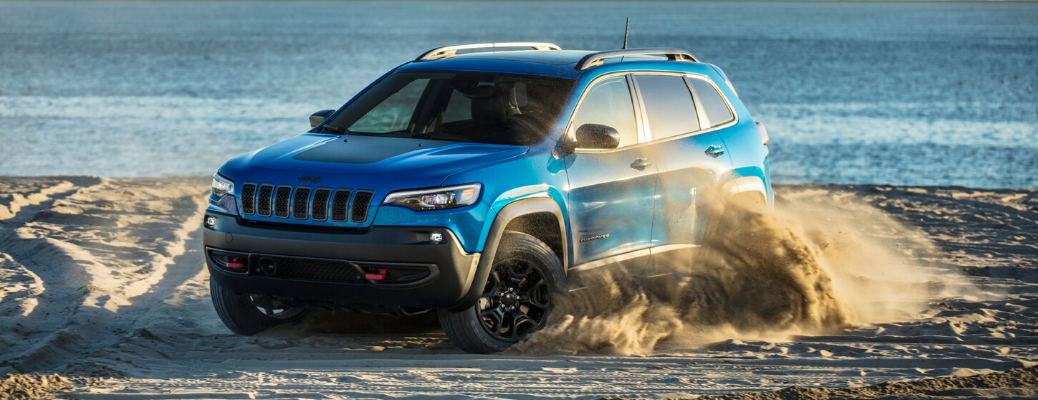 Front view of blue 2020 Jeep Cherokee Trailhawk on the beach