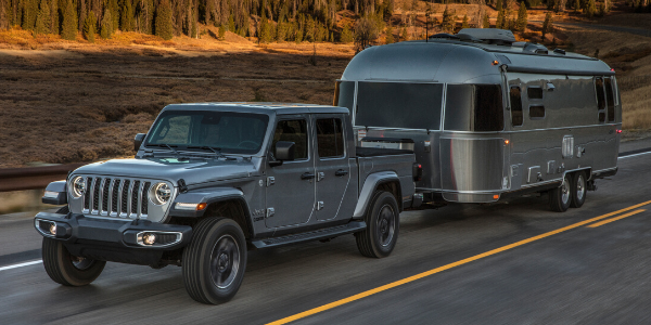 Front view of grey 2020 Jeep Gladiator Overland towing a trailer