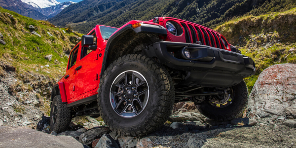 Low-angle shot of red 2020 Jeep Wrangler Rubicon rock crawling