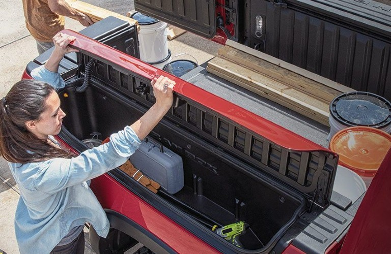 Woman looking at open ram box in trailer