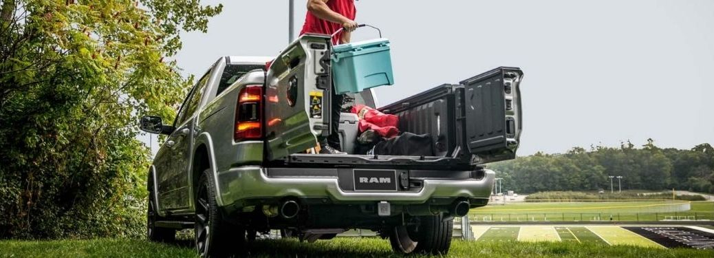 Man Standing in Bed of a 2021 Ram 1500 Cargo Bed Loading a Cooler