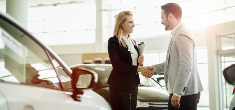 A man and a woman shaking hands inside a car dealership