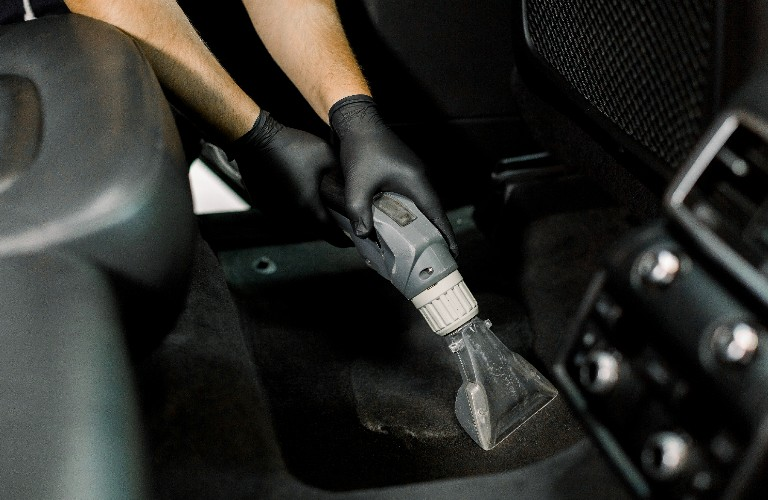 A person with black gloves on vacuuming out the floor of a vehicle