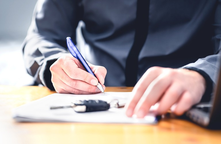 A man writing on a piece of paper with car keys resting on the paper
